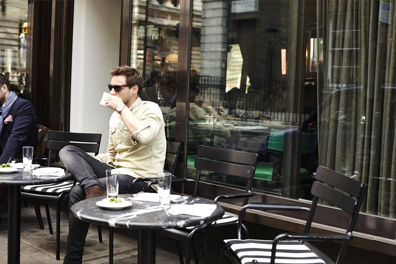 A man drinking coffee outside Cecconi's Mayfair